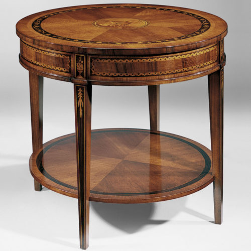 Louis XVI style round two-tier table with walnut veneer. Louis XVI table inlaid with ebony and many other woods. The inlaid design in the center of the table top features two classical figures. The ebony border on the top has an inlaid floral motif. This table is hand-crafted in Italy