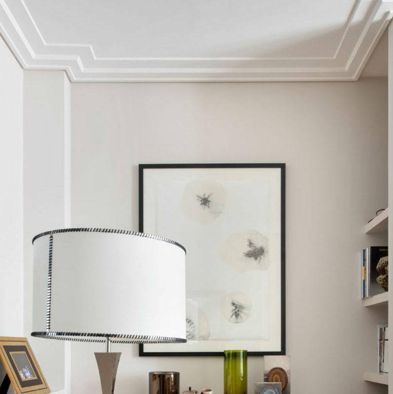 Modern flat crown molding mounding; crown molding has an asymmetrical profile with an extended top surface projection across the ceiling