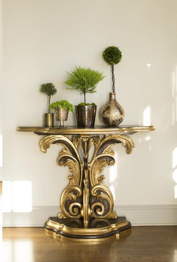 Interior with late Baroque style carved wood console in antique brown finish and antique gold leaf accents; console table is available at InvitingHome.com