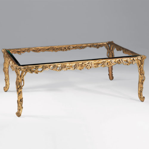 Rectangular carved wood coffee table with leaf motif. Carved coffee table has antiqued gold-leaf finish and thick beveled glass top. This carved wood table is hand-made in Italy