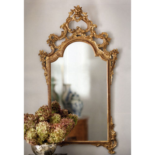This elegant carved wood mirror is hand crafted in 18th century Italian style. Decorative wall mirror has floral design with graceful scrolls. Mirror has an antiqued gold leaf finish. This mirror is hand-crafted in Italy