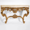 Louis XV style carved wood console with leaf scroll motif in antiqued gold leaf finish. Louis XV console has Calacotta gold marble top. This console table is hand made in Italy