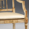 Hand-painted Sheraton style beech wood armchair with antiqued white and gold finish. Armchair has a cane seat and upholstered cushion. This armchair is hand crafted in Italy