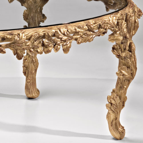 Oval carved wood coffee table with leaf motif. Carved coffee table has antiqued gold leaf finish and glass top. This carved wood table is hand-made in Italy