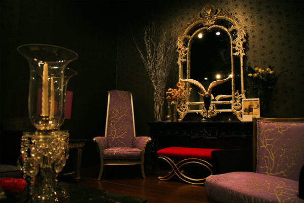 Lavish interior with glorious mirror in elaborate carved wood frame with gold leaf finish, beautiful arrangement of decorative accessories and luxury furniture; luxury decor inspiration; interior decorating ideas