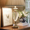 Solid brass and solid crystal table lamp. Crystal lamp has an antiqued finish, crystal finial, round base and round pleated fabric shade;
