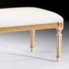 Louis XVI style carved beech wood bench with hand-painted antiqued white finish. antiqued gold leaf accents and off-white muslin upholstery. This bench is hand-crafted in Italy