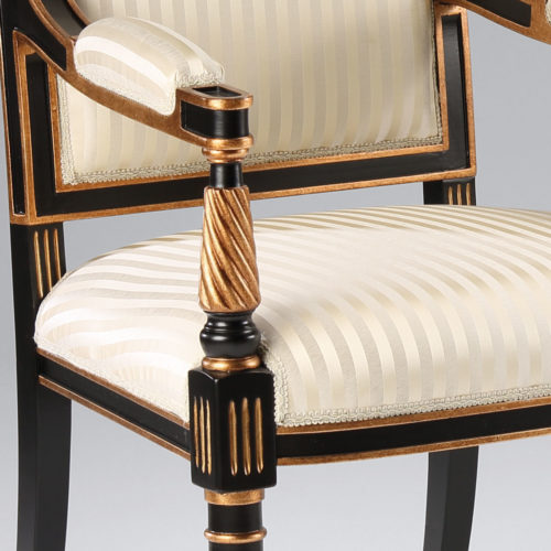 Regency style carved wood armchair in black finish with antique gold-leaf trim. The armchair has striped ivory upholstery. This upholstered armchair is hand-crafted in Italy