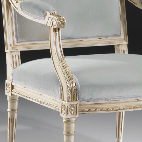 Louis XVI style carved beech wood armchair in distressed white finish with antique silver leaf trim and blue-grey upholstery. This upholstered armchair is made in Italy