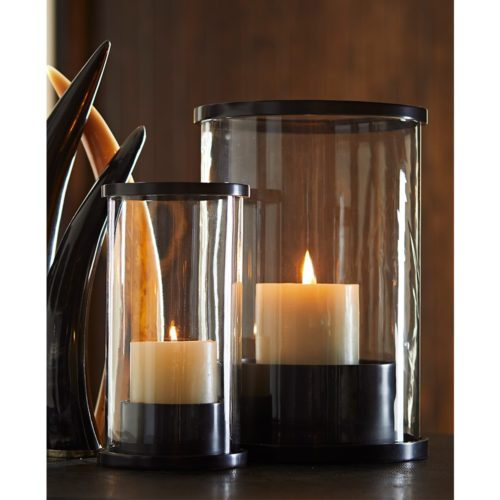 pair of elegant Bronzed Hurricane Lamps gleaming with an tranquil ambiance. Hurricane lamps are finished with bronze and are perfect for any living space.