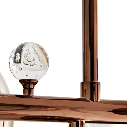 Varying sizes of seedy smoke glass globes embellish a sleek and slender steel frame that works to ground the slightly whimsical design. Small, clear crystalknobs contrast beautifully with the brown nickel finish
