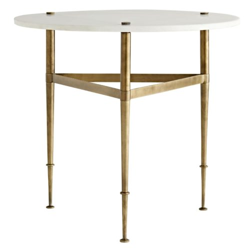 A white marble top adds airiness and classic grandeur to a simple iron base finished in antique brass. Slender legs that pierce through the top andtaper down to decorative feet are united by an iron band, delivering a geometric touch.