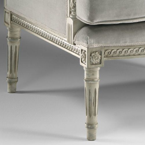 Louis XVI style carved beechwood armchair in antiqued white finish with antiqued silver leaf trim. Louis XVI armchair has grey upholstery. This armchair is handcrafted in Italy