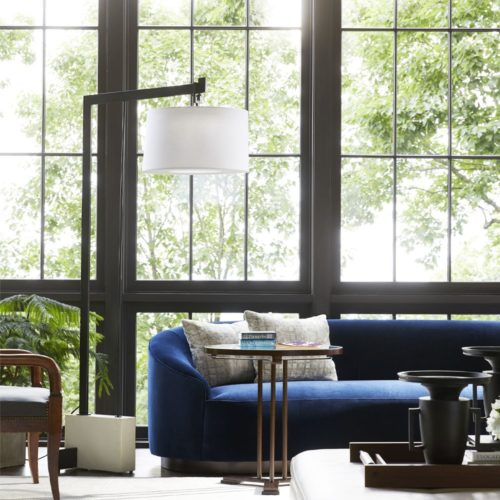 Warm and inviting open style living room with natural hues. Elegant blue velvet couch paired with leather wing chair and lovely porcelain lighting.