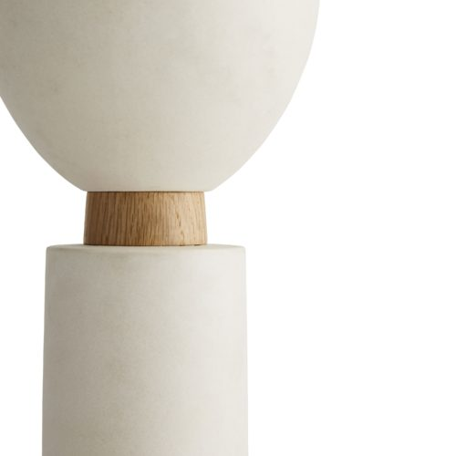 The three ceramic forms play with mixed materials, juxtaposing matte ceramic against oak plinths.